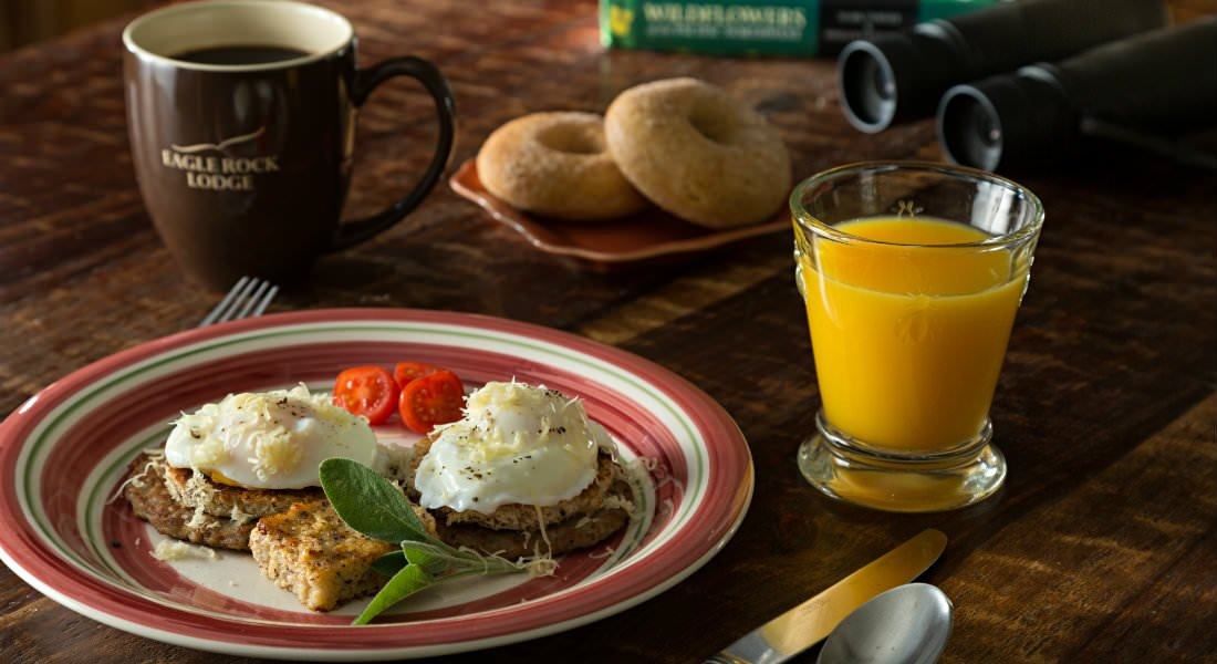 Poached eggs plated over sausage patties near silverware, a glass of orange juice and a coffee mug.