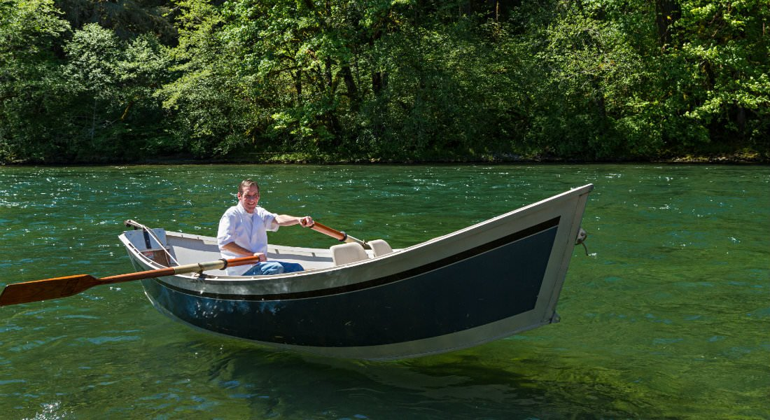 A man smiling, holding two oars in a rowboat on the shimmering green river with trees behind him.