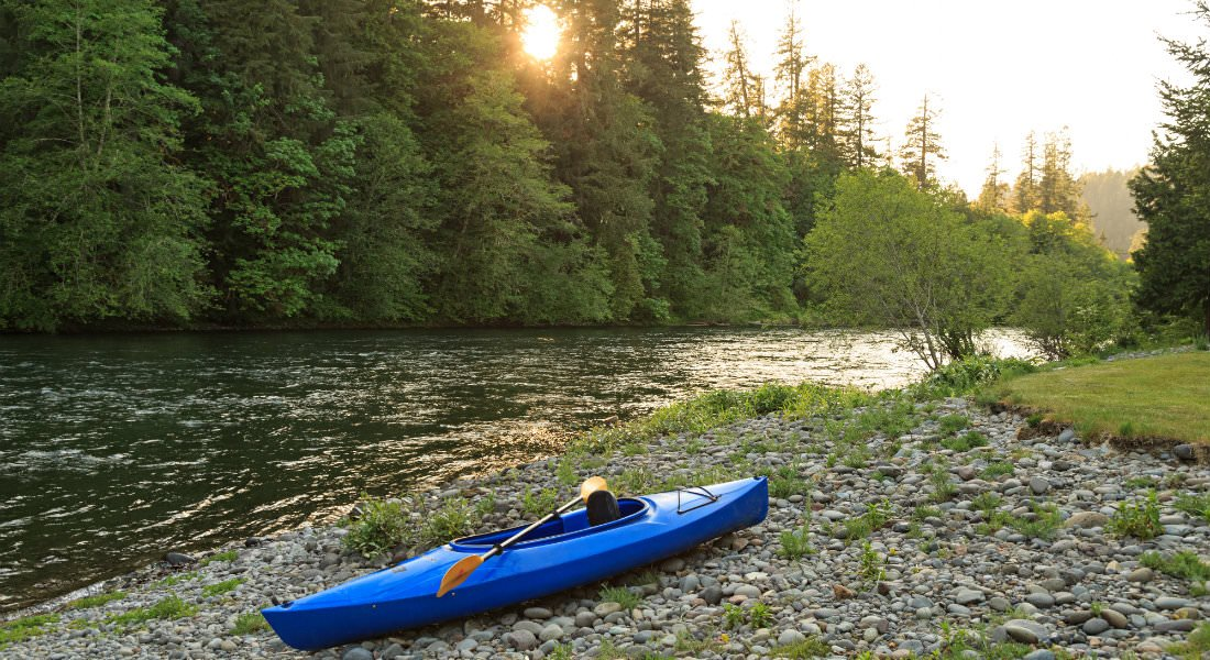 A blue kayak on the rocky beach of the shimmering river with the sun setting in the forest.