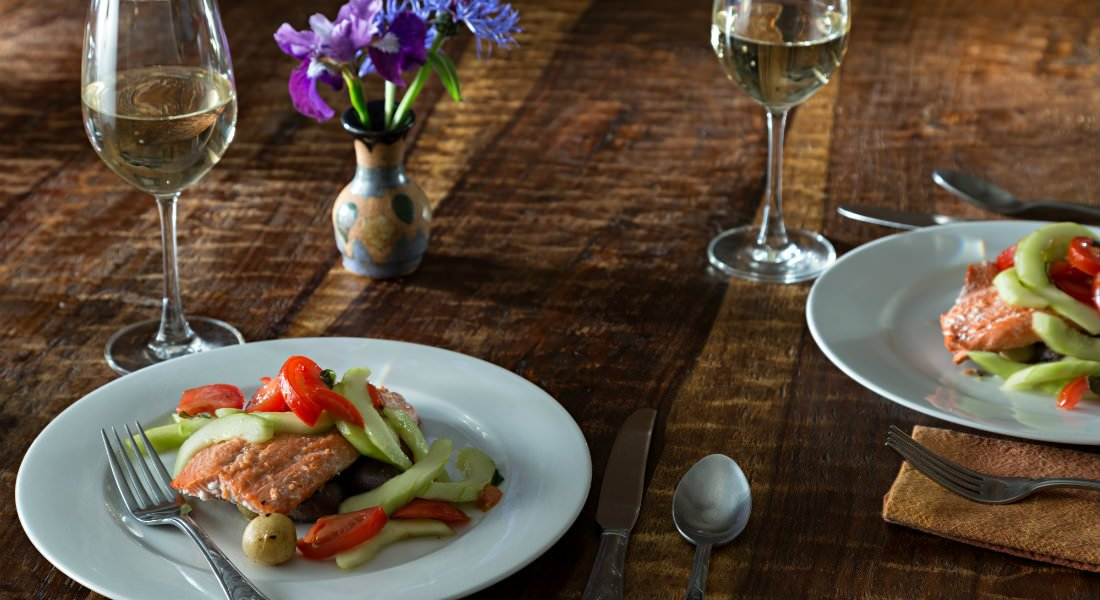 Plates of salmon with fresh vegetables, silverware, glasses of white wine and a vase of purple flowers.