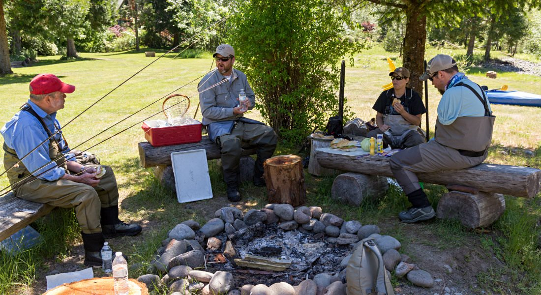 Three men and one woman in fishing gear sit on brown logs near a firepit eating lunch.
