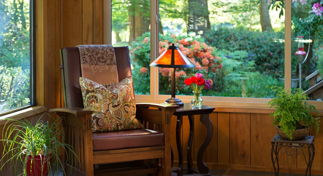 A comfortable brown chair with a paisley pillow near a Craftsman lamp and windows.