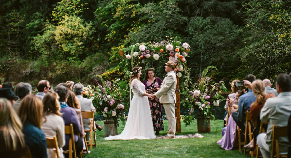 A couple being married by an officiant on the green lawn near a flowered trellis before a seated audience.