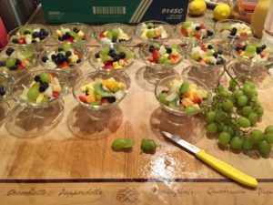 Glass bowls on a wooden table filled with blueberries, green grapes, kiwi, apples and honeydew.