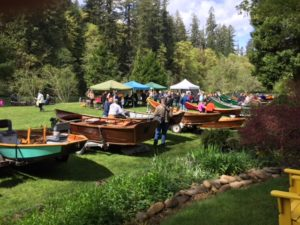 Multiple boats on trailers on the green lawn with boaters milling about under colorful canopies.