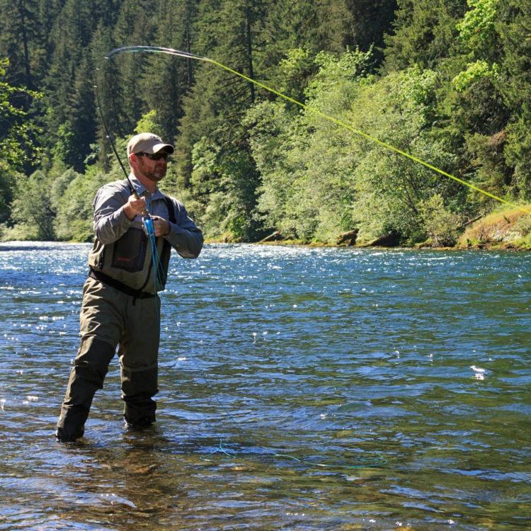 Man with beard fly-fishing in river with green woods in the background