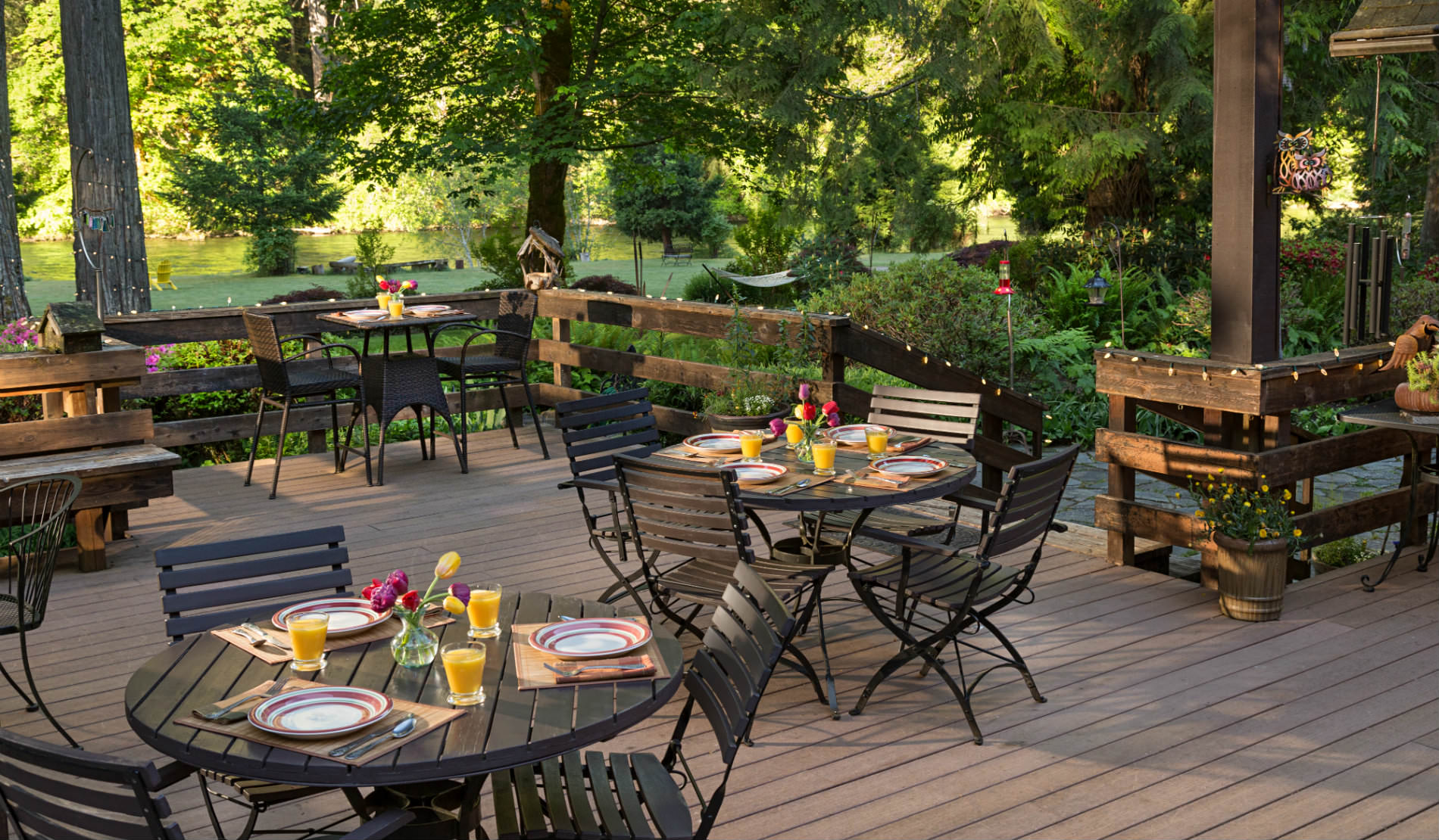 Wooden deck with lights and small wooden tables set with dishes