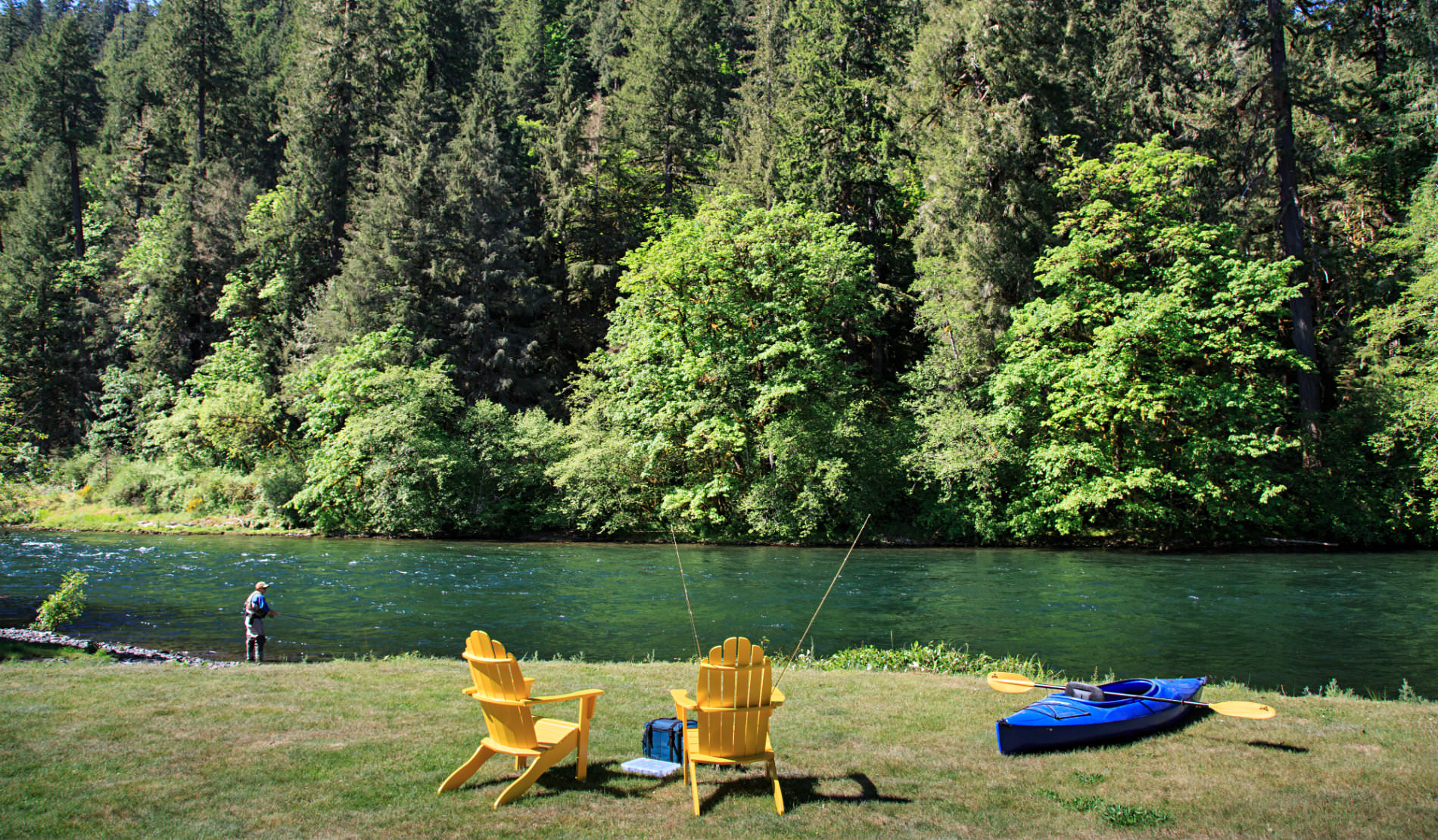 Wooded area on edge of river bank with two wooden chairs and a blue kayak and man fishing