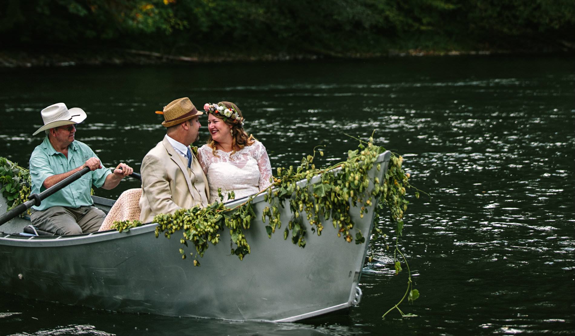 Happy Bride and Groom being rowed in a metal rowboat with yellow flowers decked on front