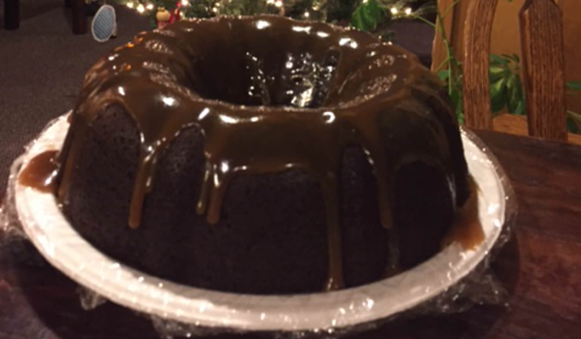 A Guinness Stout chocolate cake smothered in rich, brown chocolate incing on a white plate.