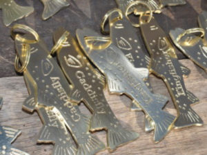 Golden fish shaped keychains and rings inscribed with room names on them on a wooden table.
