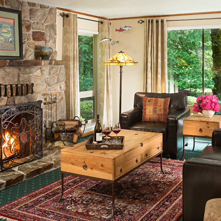 Large stone fireplace facing two leather club chairs with large windows viewing greenery outside