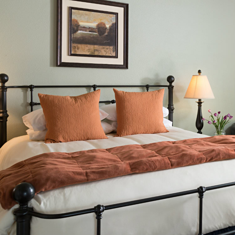 Large iron bedstead with soft rust and white bedding, lit lamp and chair with green walls