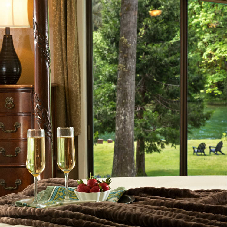 Bed with champagne glasses and berries facing large window with view of green trees and river