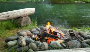 Large rock surounded firepit with a burning fire on the bank of the river flowing by