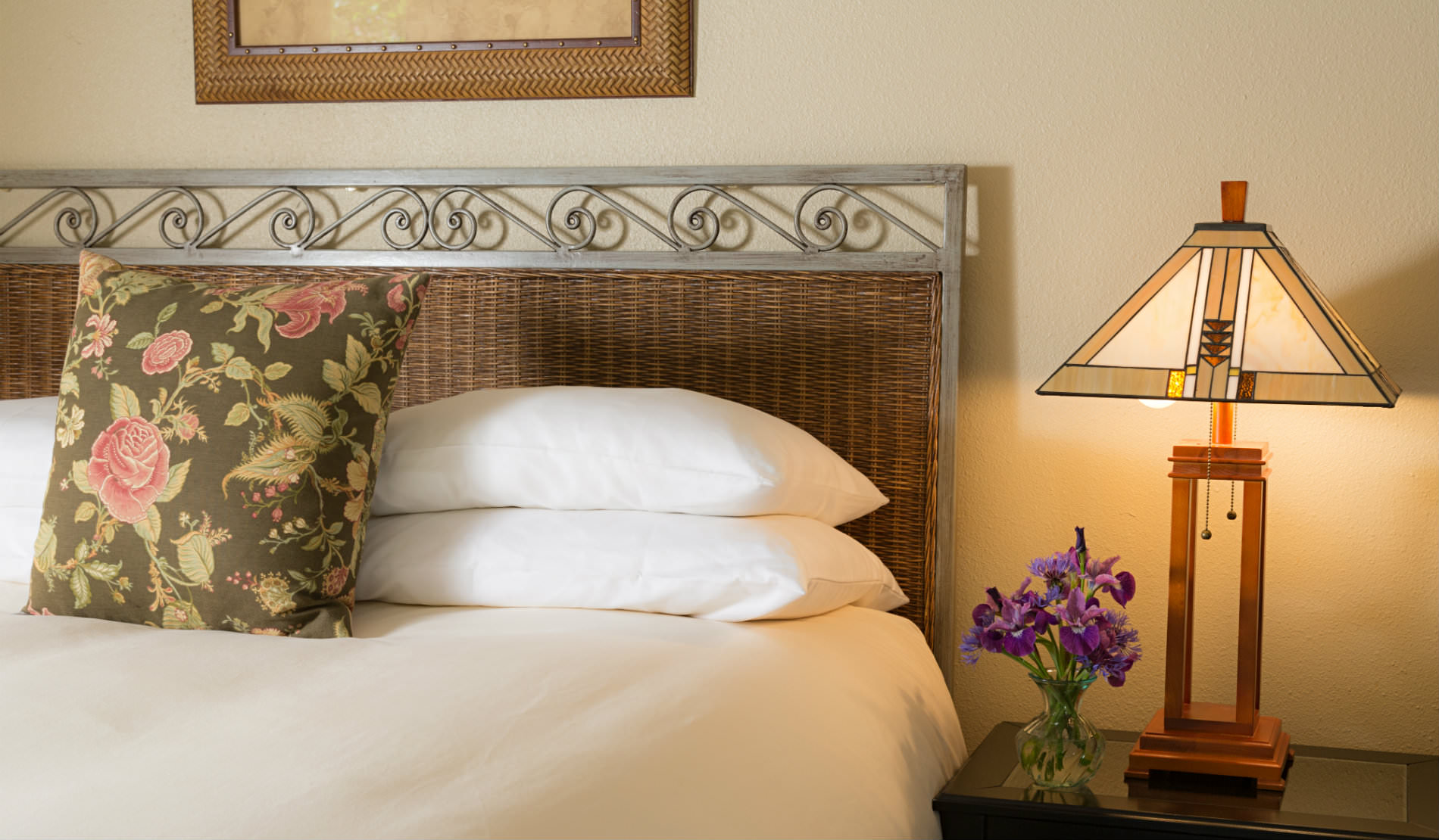 Soft white bedding and pillows on bed next to sidetable with craftsman-style lamp and purple flowers.