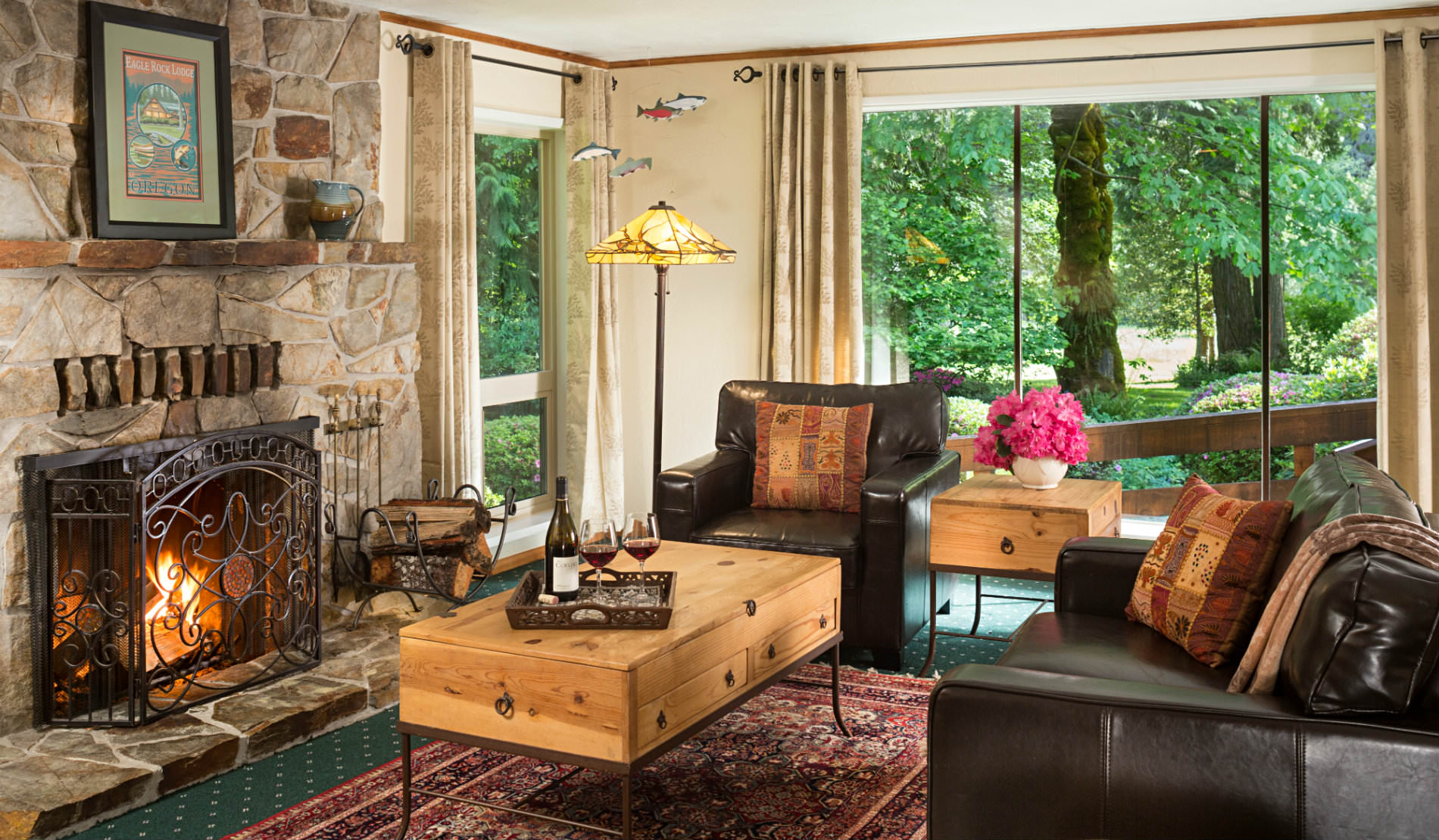 Large stone fireplace facing two leather club chairs with large windows viewing greenery outside.