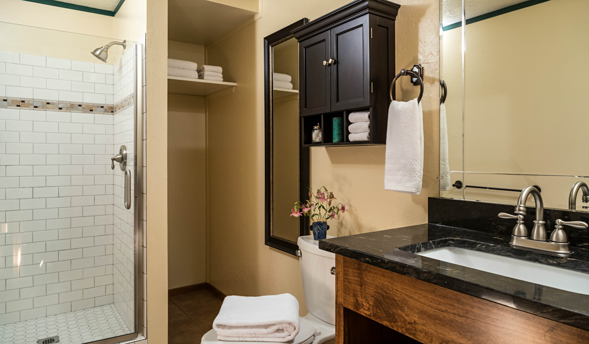 White tiled shower with glass door, wooden vanity with black counter, beige walls.