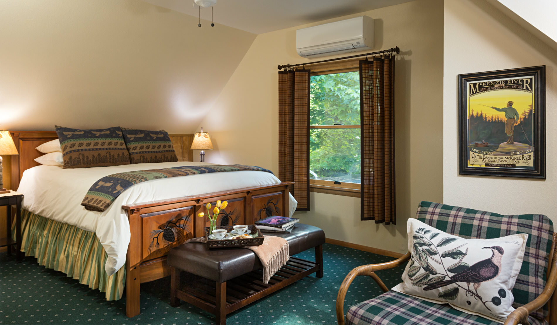 Large wooden bed with white bedding, plaid chair, large wood window with brown drapes.