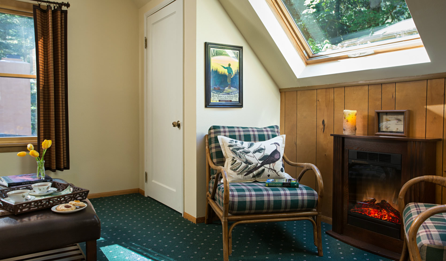 Skylight over plaid chairs with green carpet and large window with brown curtains.