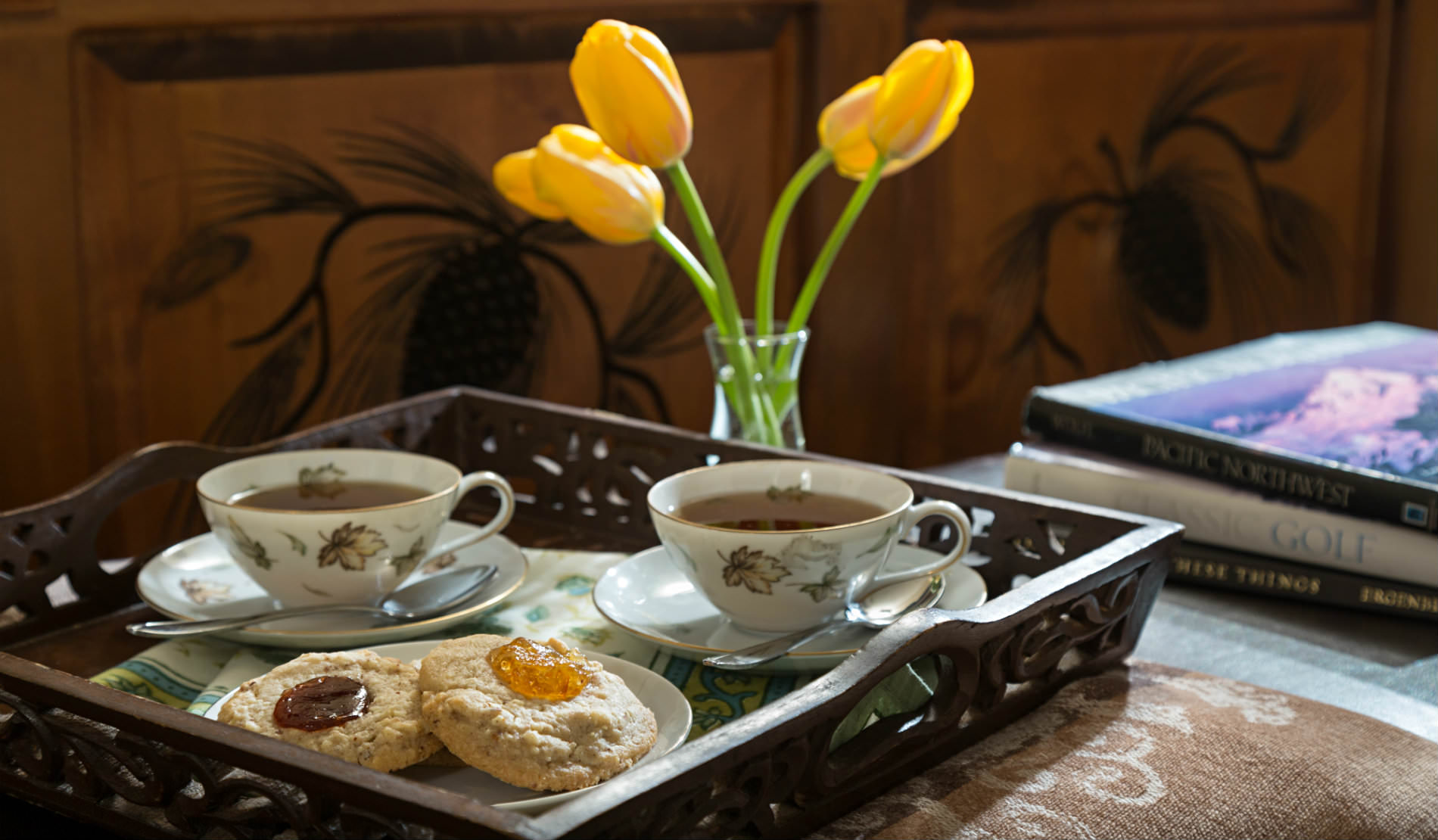Cookies and tea on wooden server with yellow tulips and stack of books.