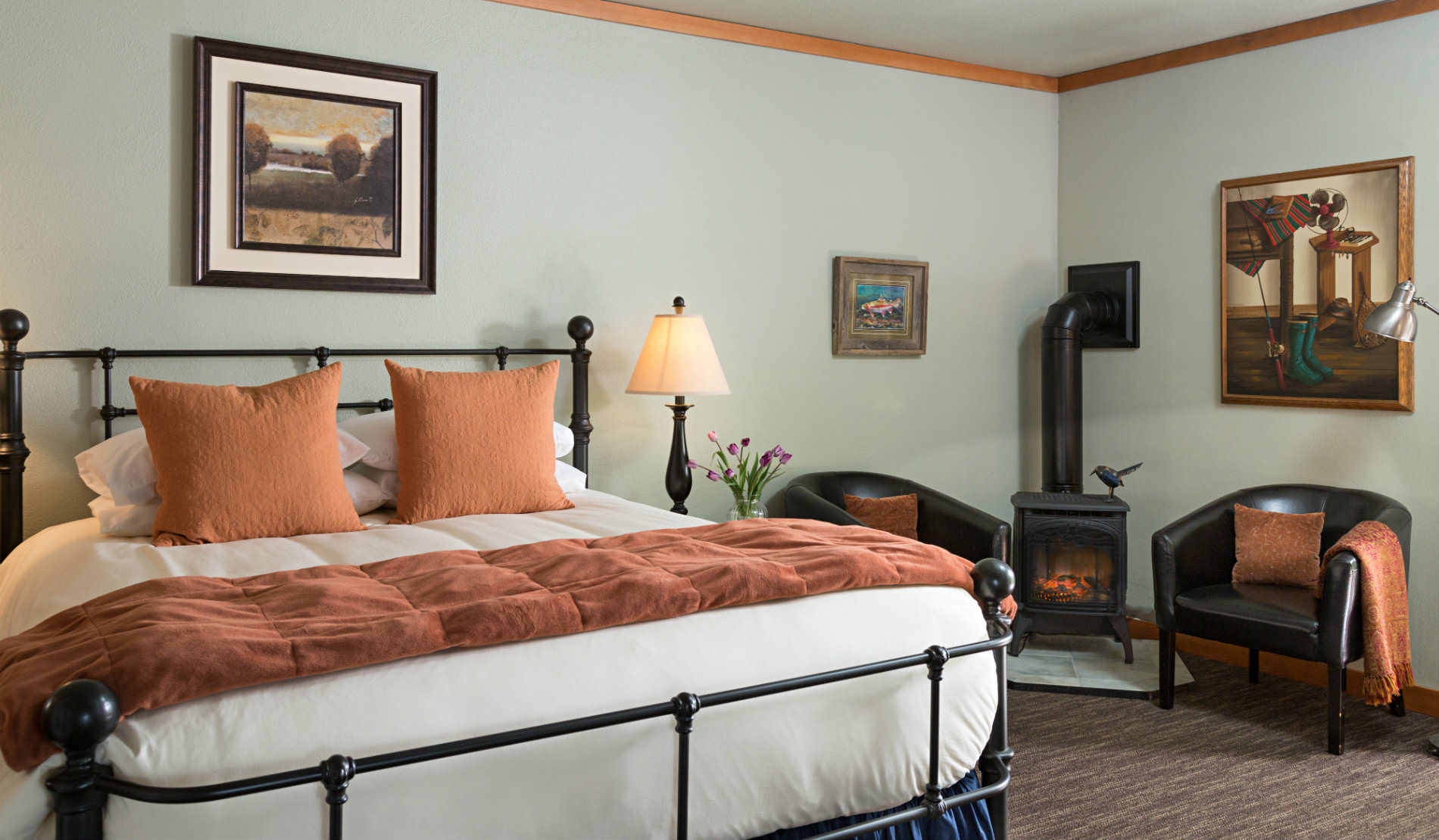 Large iron bedstand with soft rust and white bedding, two chairs beside wood burning stove.