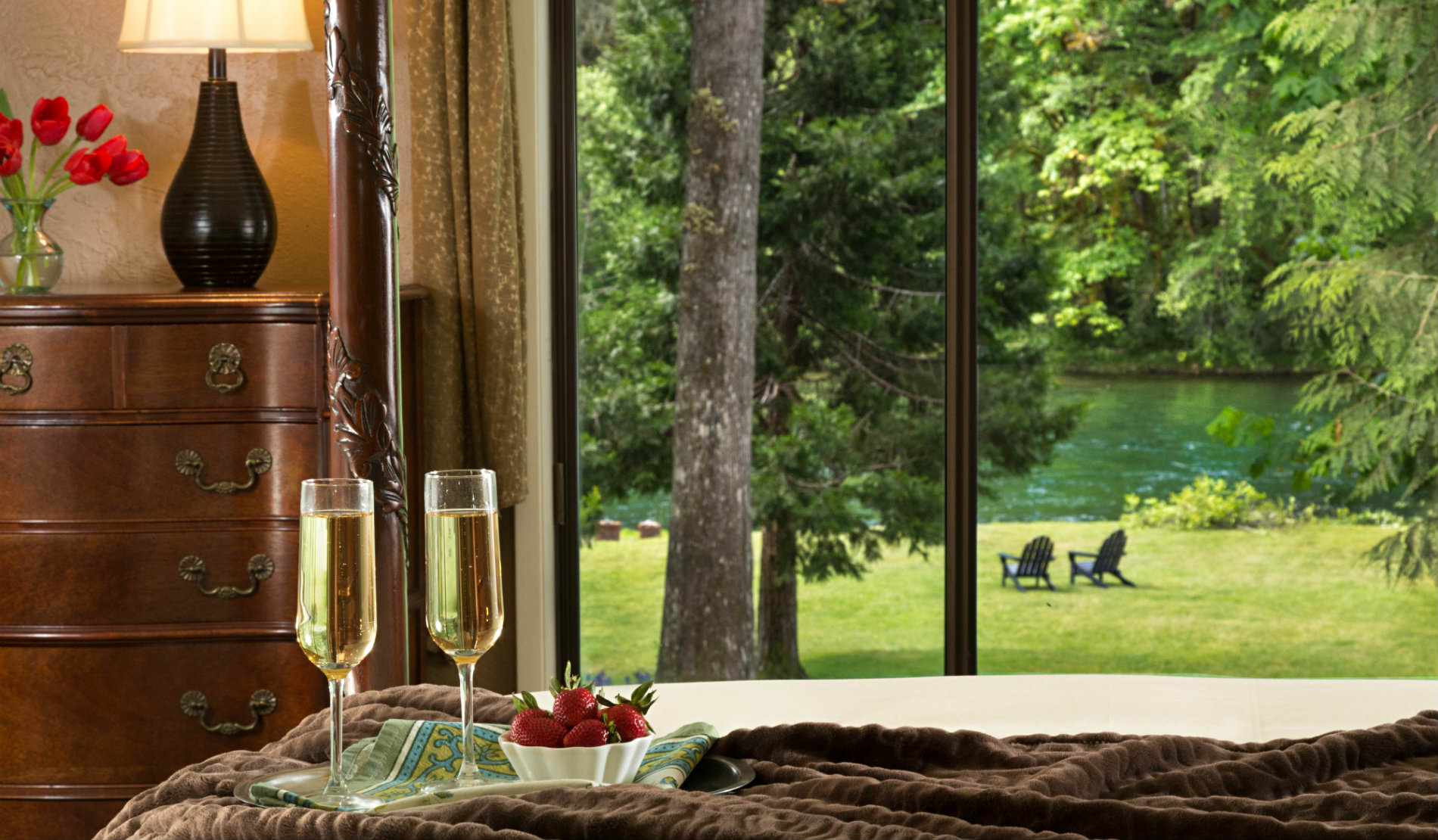 View from bed with wine glasses and strawberries to brown dresser and grassy area and river, two chairs
