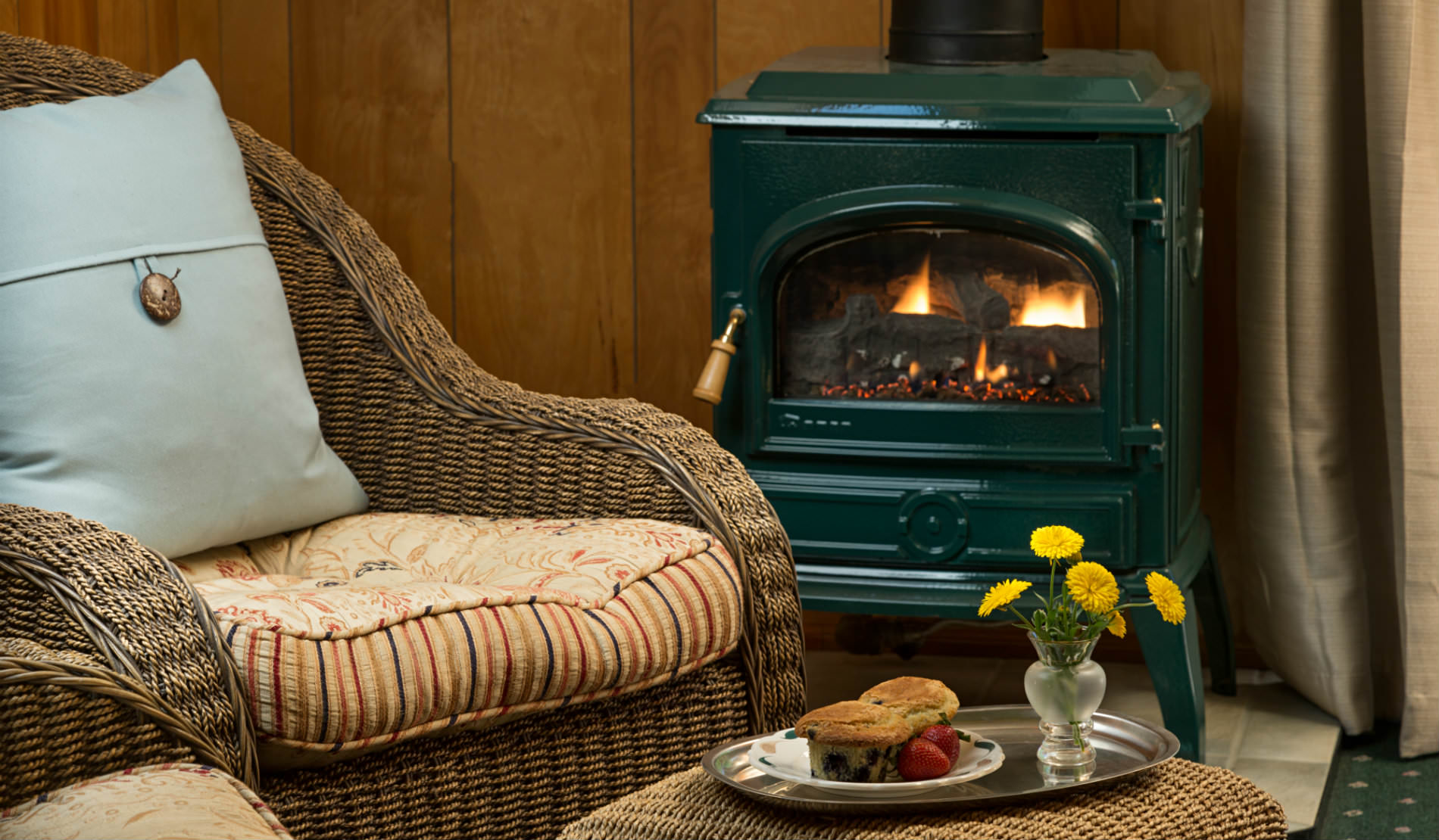 Brown wicker chair with green and patterend cusions in front of wood burning stove