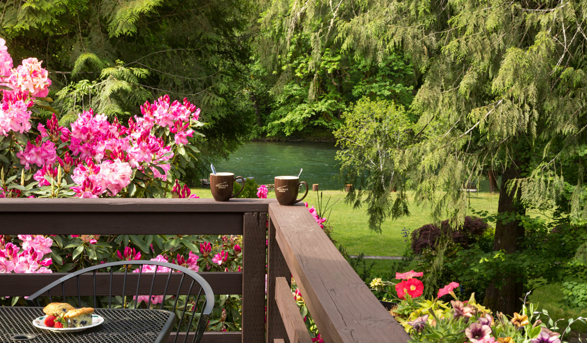 Corner of wooden deck with coffee cups on ledge, pink flowers and green tree in background
