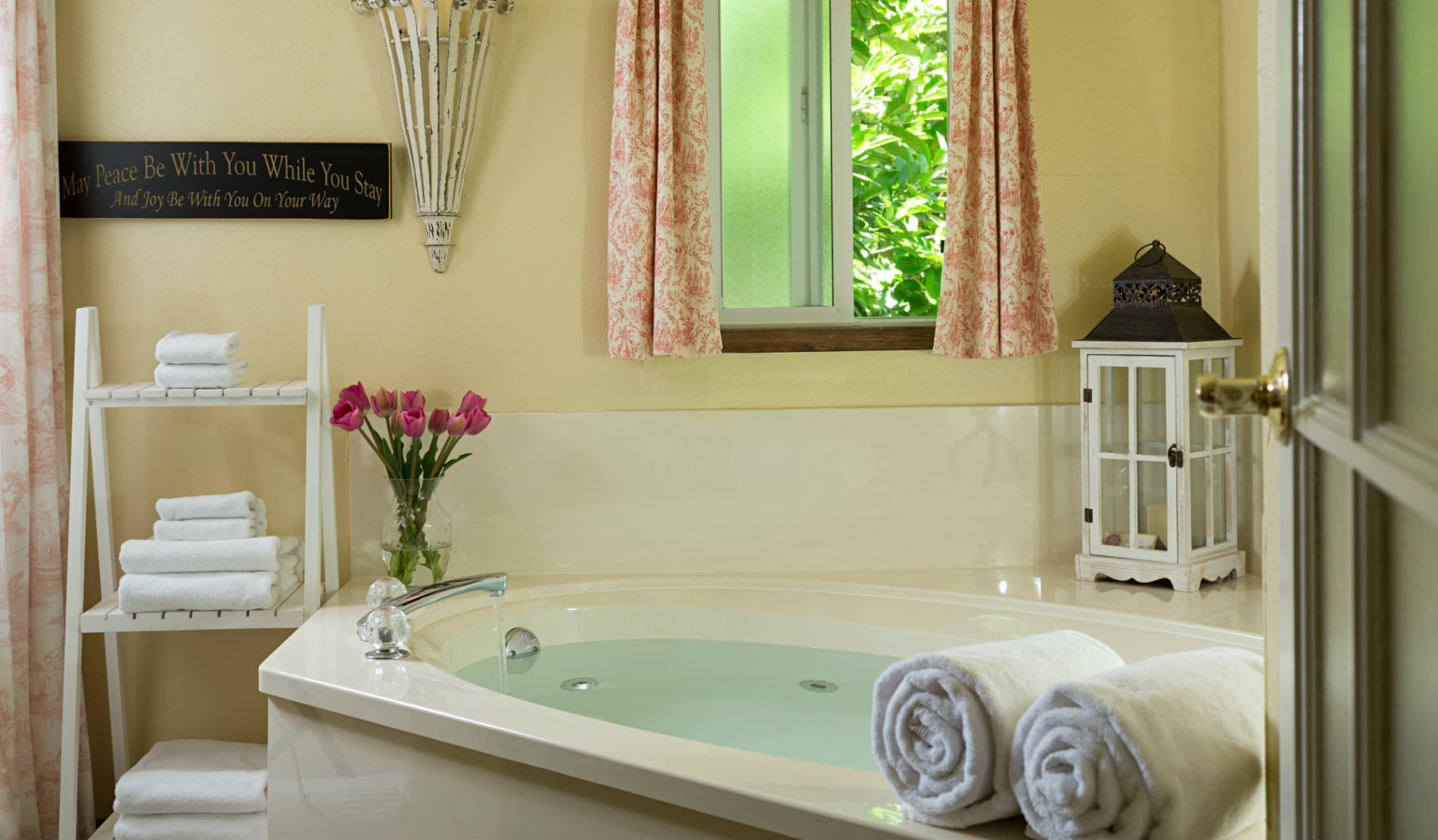 Whirlpool bath with white towels, pink flowers and window open to green tree.