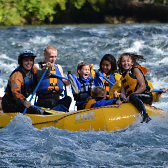 A man, a woman, and four children whitewater rafting in a yellow raft, going down Level 3 rapids..