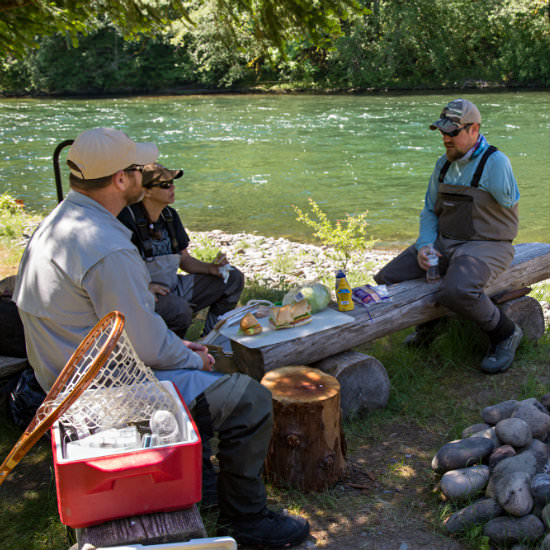 Two men and a woman in hats and fishing gear sitting on wooden benches having lunch near a red cooler.
