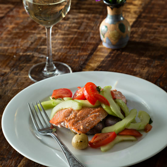 Pink salmon on white plate with vegetables and glass of white wine