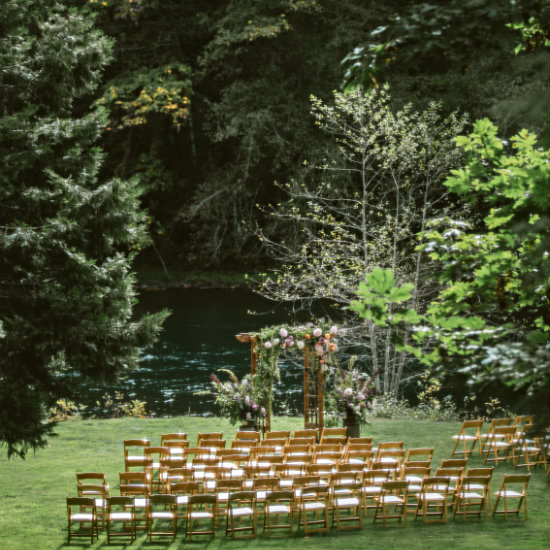 Wooden chairs set up for wedding on lawn in front of flower decked arch with woods in background