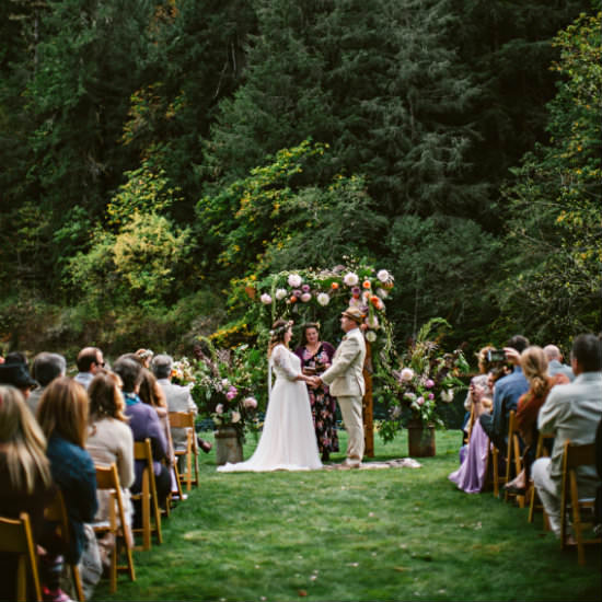 Bride and Groom at flower-bedecked arch, guests in wooden chairs on grassy lawn