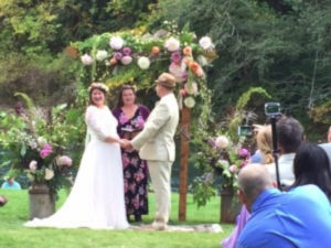 A couple smiles near their officiant and a flowered trelllis as guests look on from the green lawn.