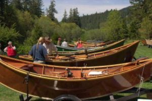 A group of people mill about a collection on wooden boats on trailers with lush green trees behind them.